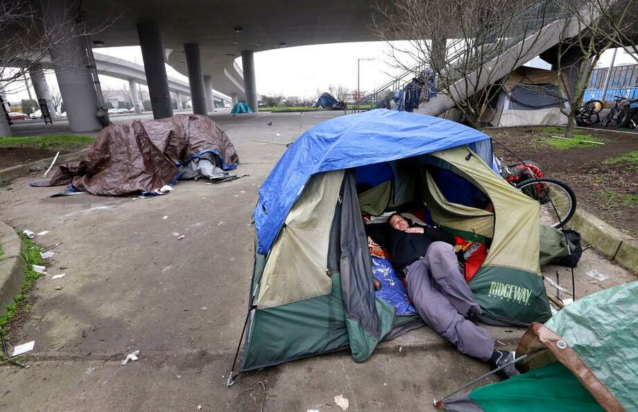 In this Feb. 9, 2016 file photo, a man lies in a tent with others camped nearby, under and near an overpass in Seattle. Microsoft pledged $500 million to address homelessness and develop affordable housing in response to the Seattle region's widening affordability gap. The company, which plans a news conference Thursday, Jan. 17, 2019, will split the funds three ways. Photo: Associated Press/Elaine Thompson