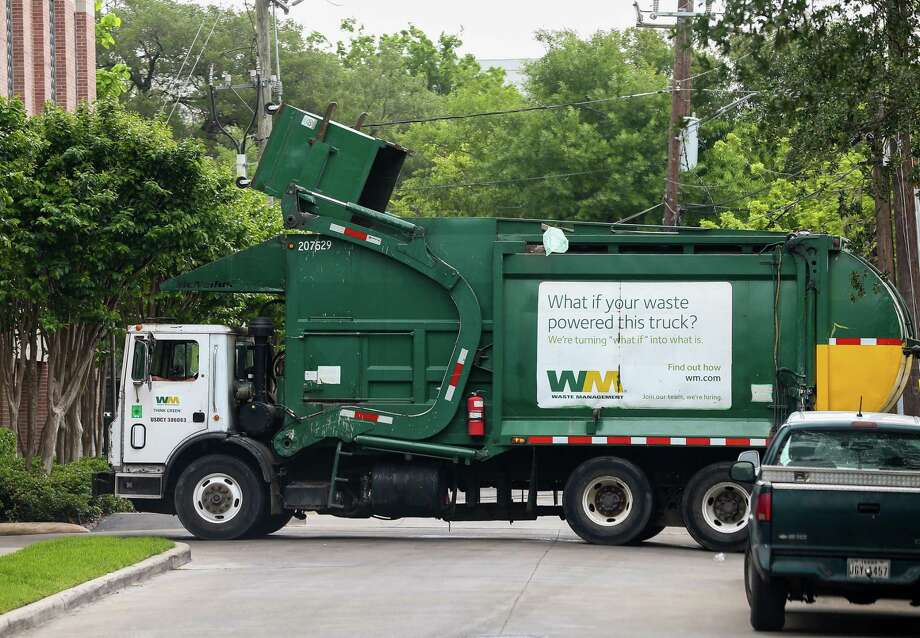 A Waste Management garbage truck pickups a dumpster on Milford Street near Montrose Boulevard Friday, April 13, 2018, in Houston. ( Godofredo A. Vasquez / Houston Chronicle ) Photo: Godofredo A. Vasquez, Staff Photographer / Houston Chronicle