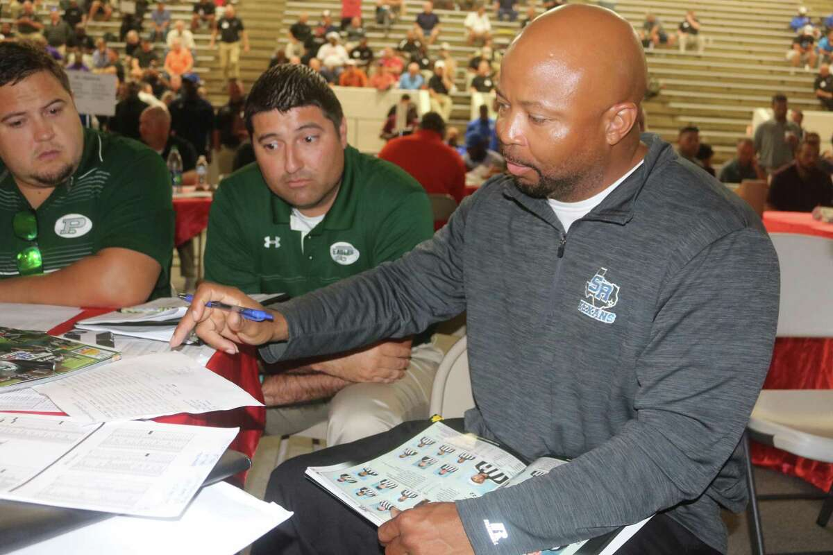 New Sam Rayburn head coach  Demond Stafford and new Pasadena head coach David Zapien confer over what officiating crew they want for this year's game during the Region III Selection Day at Phillips Fieldhouse.
