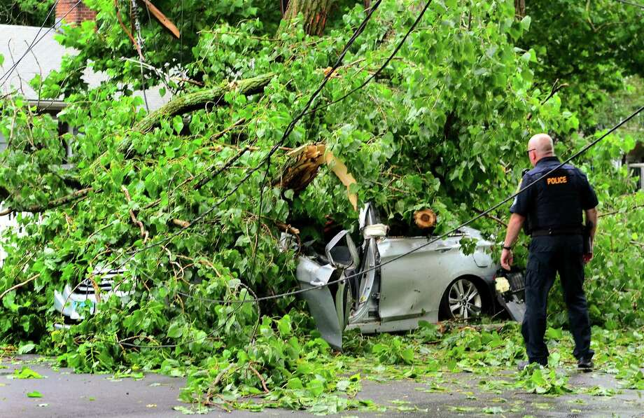 A car, with an occupant who was rescued from, is still covered by a tree which fell on it along Park Ave Bridgeport, Conn., on Wednesday July 17, 2019. Due to live wires that fell, Bridgeport and Fairfield firefighters had to wait as long as an hour before they could remove the victim. Photo: Christian Abraham / Hearst Connecticut Media / Connecticut Post