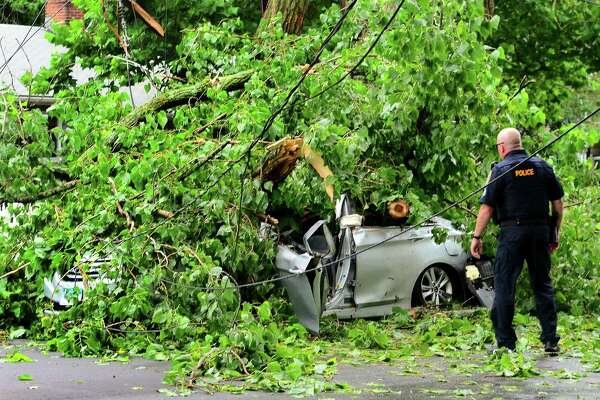 A car, with an occupant who was rescued from, is still covered by a tree which fell on it along Park Ave Bridgeport, Conn., on Wednesday July 17, 2019. Due to live wires that fell, Bridgeport and Fairfield firefighters had to wait as long as an hour before they could remove the victim.