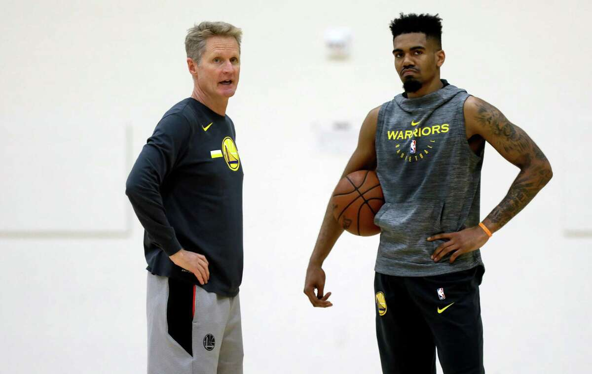 Golden State Warriors head coach Steve Kerr converses with rookie Jacob Evans III during practice in Oakland.