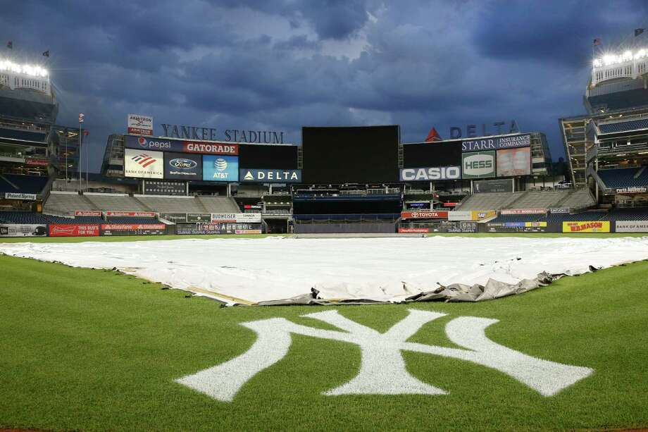 Threatening skies are seen above the tarp-covered Yankee Stadium field after a baseball game between the New York Yankees and the Tampa Bay Rays was postponed by predicted severe thunderstorms, Wednesday, July 17, 2019, in New York. (AP Photo/Kathy Willens) Photo: Kathy Willens / Copyright 2019 The Associated Press. All rights reserved.