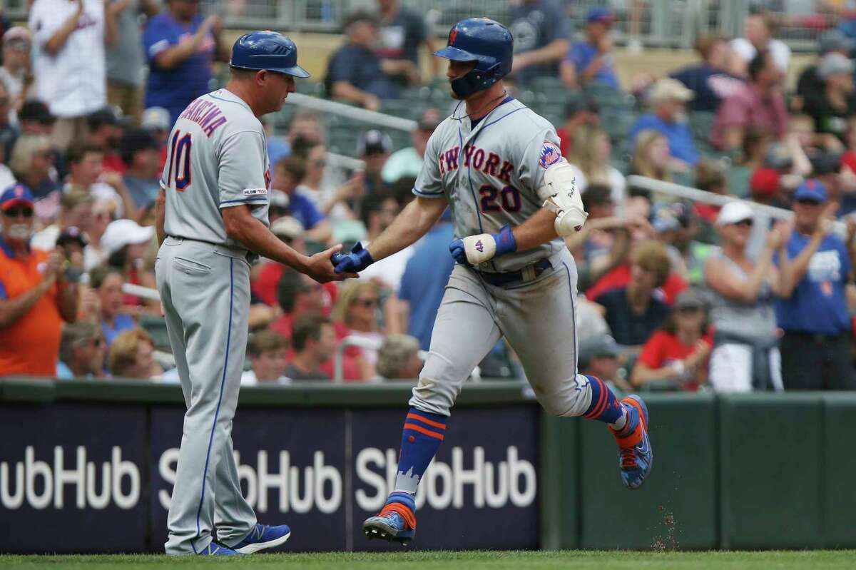 New York Mets' Pete Alonso high fives third base coach Gary DiSarcina after hitting a home run during the eighth inning of a baseball game Wednesday, July 17, 2019, in Minneapolis. The Mets won 14-4. (AP Photo/Stacy Bengs)