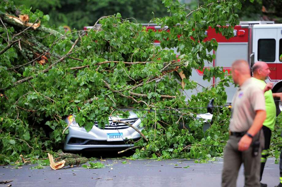 A car, with an occupant who was rescued from it, is still covered by a tree which fell on it along Park Ave Bridgeport, Conn., on Wednesday July 17, 2019. Due to live wires that fell, Bridgeport and Fairfield firefighters had to wait as long as an hour before they could remove the victim. Photo: Christian Abraham / Hearst Connecticut Media / Connecticut Post
