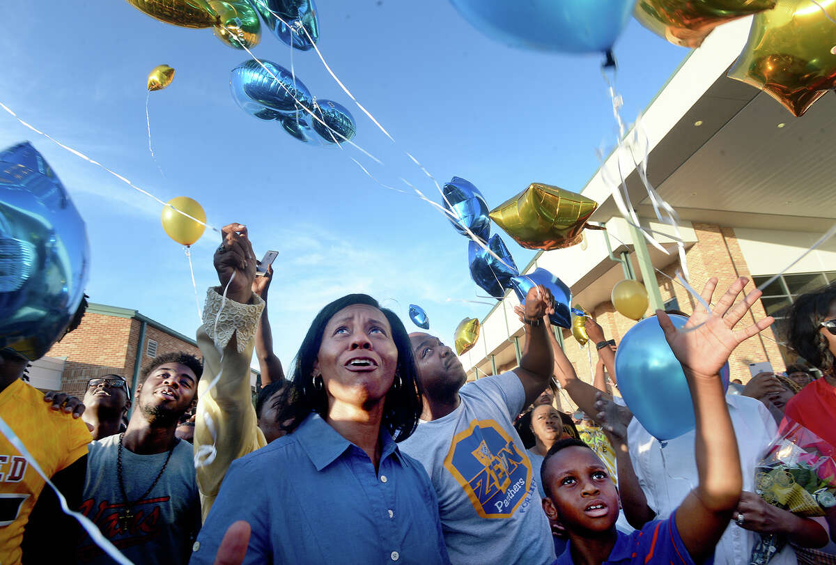 Ed Taylor's sister Monica Reynolds looks up as balloons float into the sky as she and others gathered for a release during the memorial service for Ed Taylor, a former Ozen football head coach and assistant coach for Beaumont United at United James F. Jackson Center for the Performing Arts Wednesday. Taylor passed away last weekend. Photo taken Wednesday, July 17, 2019 Kim Brent/The Enterprise