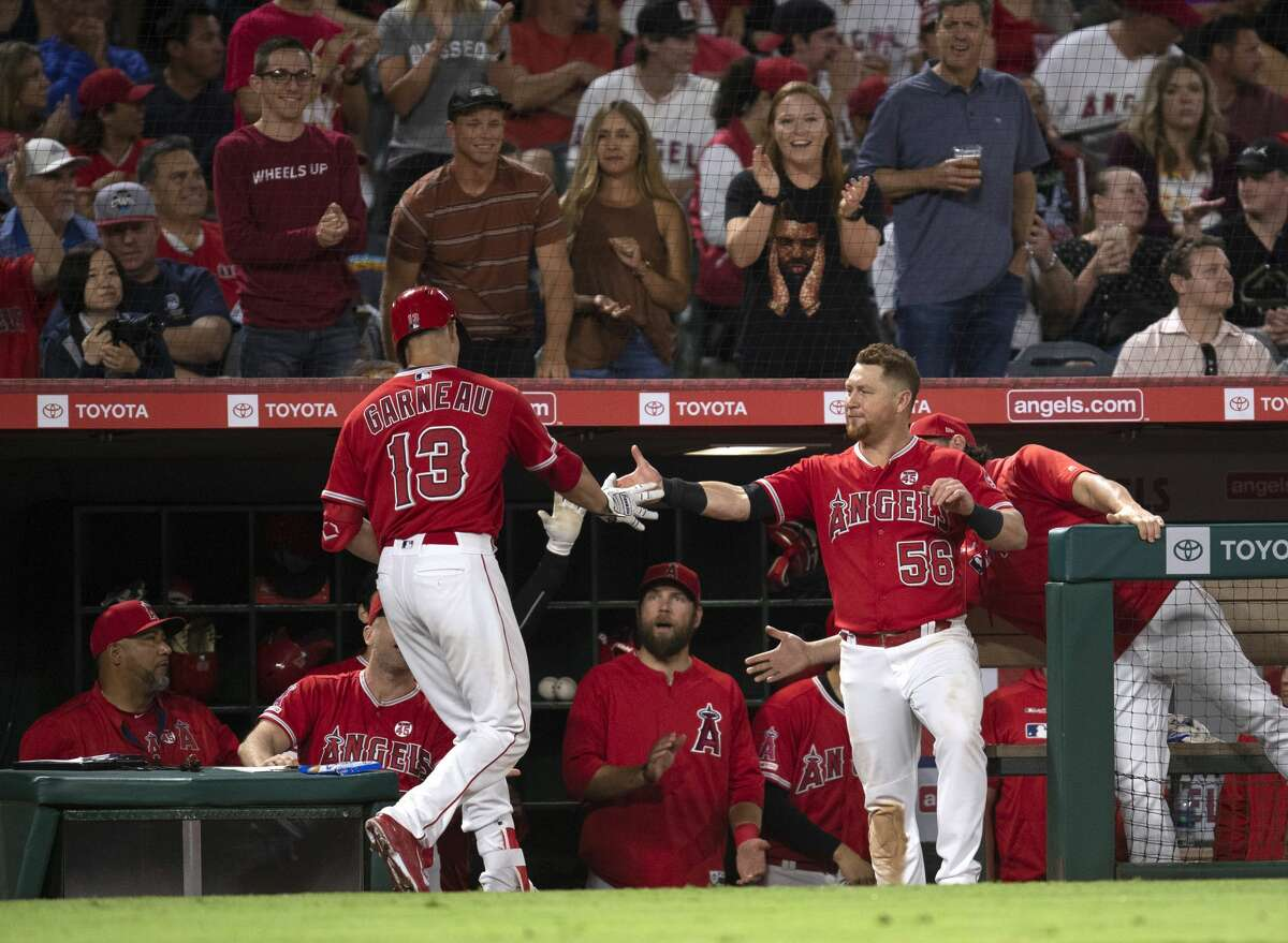 Los Angeles Angels' Dustin Garneau, left, is greeted by Kole Calhoun, right, after hitting a solo home run during the fifth inning of the team's baseball game against the Houston Astros in Anaheim, Calif., Wednesday, July 17, 2019. (AP Photo/Kyusung Gong)