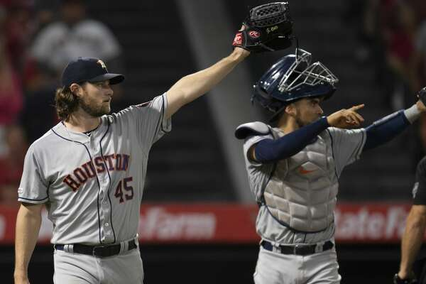 Houston Astros starting pitcher Gerrit Cole, left, and catcher Robinson Chirinos points towards left fielder Josh Reddick after Reddick threw out Los Angeles Angels' Andrelton Simmons at home plate in a baseball game in Anaheim, Calif., Wednesday, July 17, 2019. (AP Photo/Kyusung Gong)