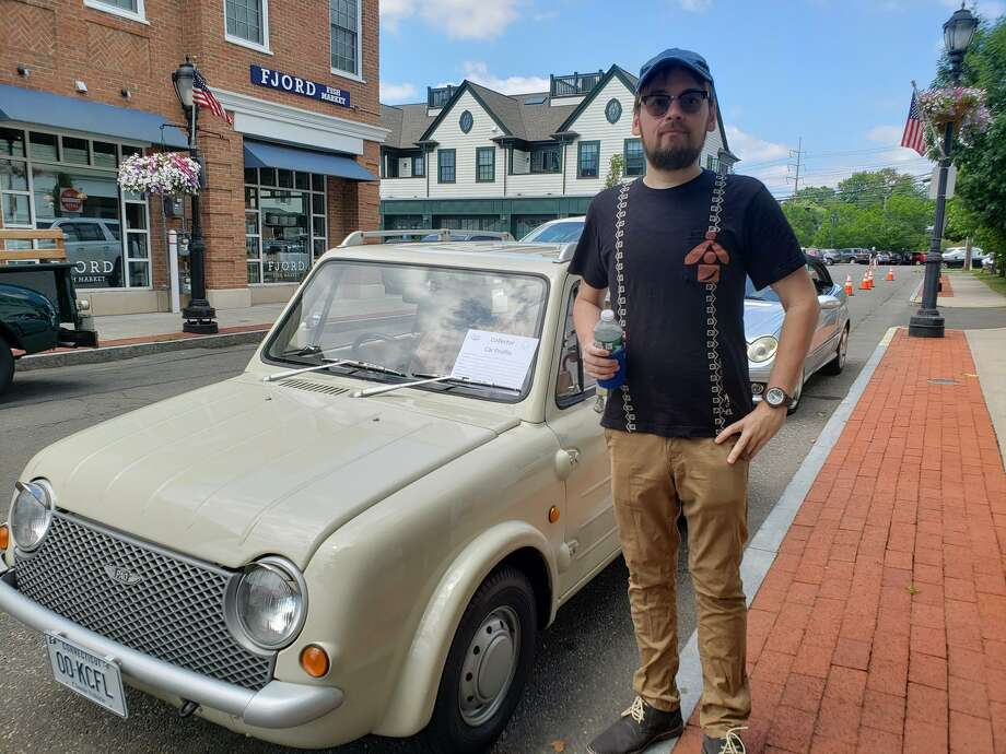 Norwalk resident Richard Errington stands in front of his 1989 Nissan Pao, a Japanese car he imported. The Collectible Car Show took place on Saturday, July 13, at the Darien Sidewalk Sales and Family Fun Days on Day Street and behind Laurel Road Bank on Post Road. Photo: Sandra Diamond Fox / / Connecticut Post