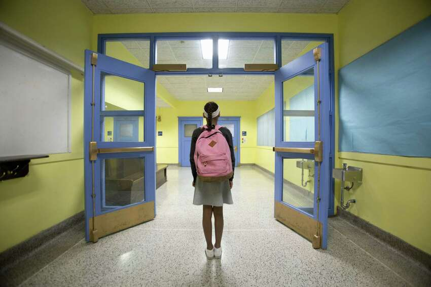 Rear view of eleven-year-old girl looking down school corridor.