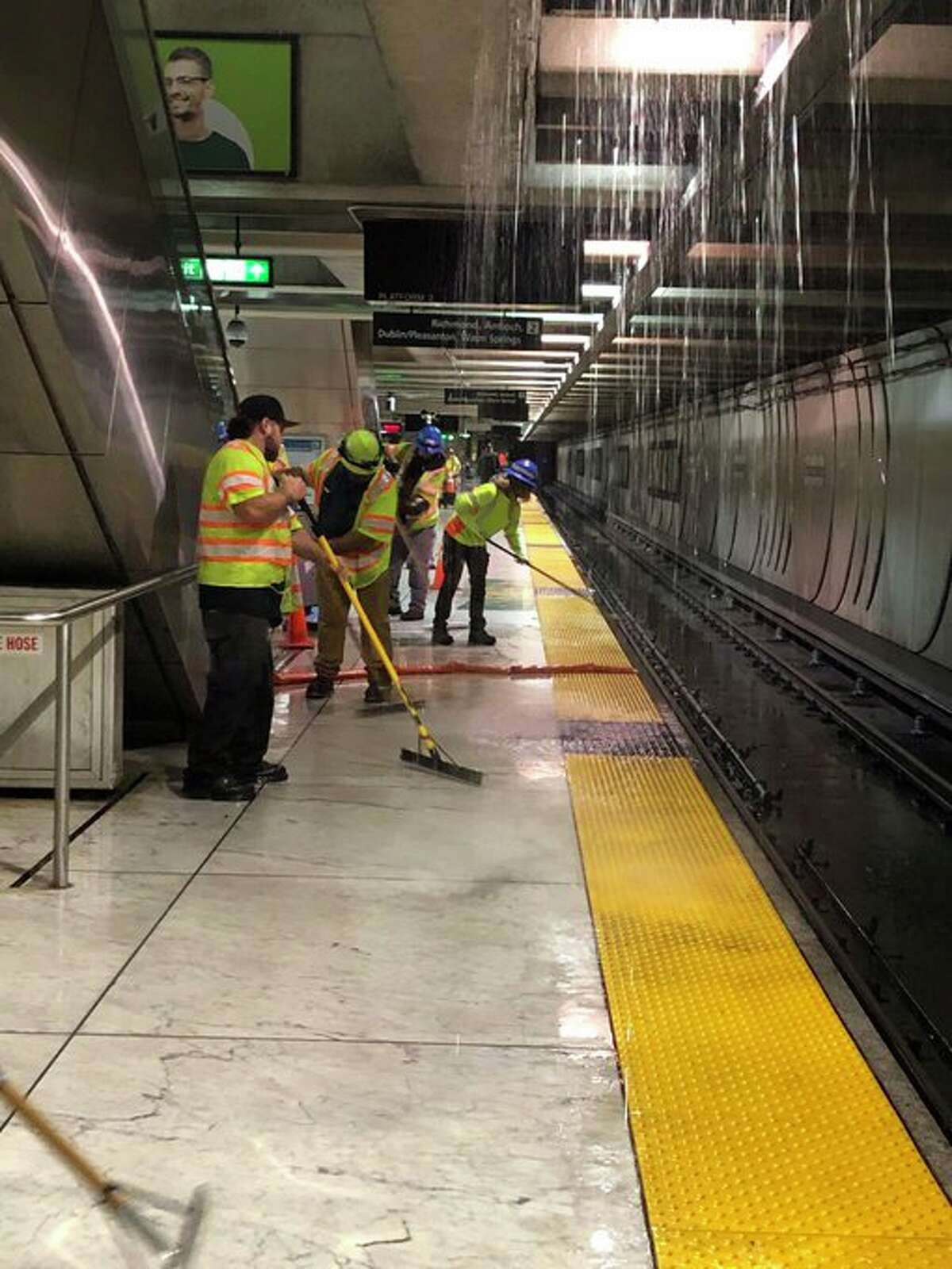 BART shared this photo of employees dealing with flooding at Embarcadero station due to flooding from the Muni level pouring into the station.