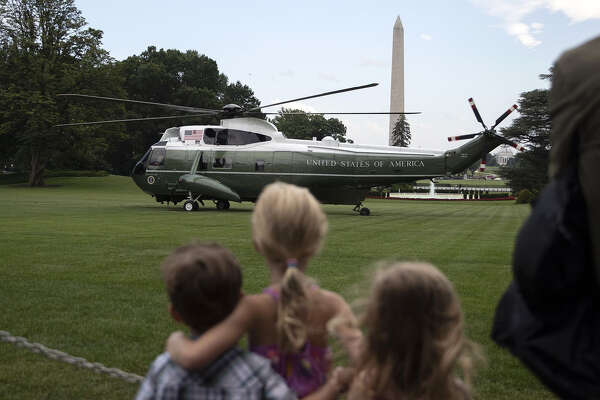 Visitors watch as Marine One, carrying President Trump, prepares to takes off on the South Lawn of the White House in Washington on July 17, 2019. MUST CRECIT: Bloomberg photo by Alex Edelman.