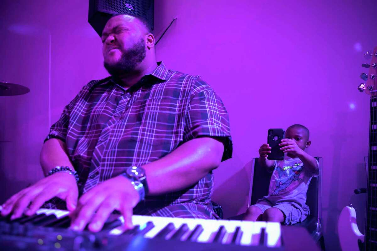 Zach Fisher plays the keyboard while his six-year-old son Cameron films him during the second Shift Christian Lounge event on Saturday, July 5, 2019, at God Encounter Church in northwest Houston.