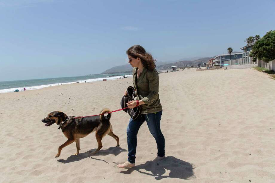 Anne Enna and Roscoe walks her dog on the beach near her home in Ventura, Calif., on July 3, 2019. Photo: Photo For The Washington Post By Allison Zaucha / Allison Zaucha