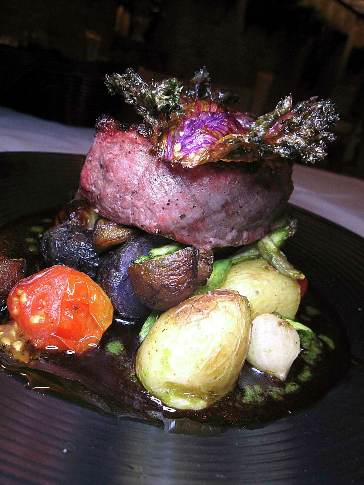 A beef tenderloin steak comes with roasted mushrooms, asparagus, tomatoes and potatoes at Cappy's.