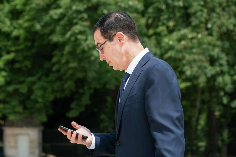 Treasury Secretay Steven Mnuchin checks his mobile phone at the Group of Seven (G-7) finance ministers and central bank governors meeting in Chantilly, France, on July 18, 2019. Photo: Bloomberg Photo By Jasper Juinen. / © 2019 Bloomberg Finance LP