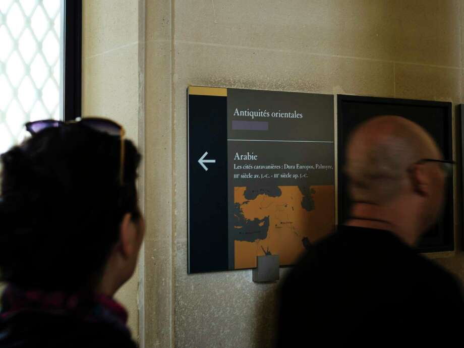 Visiotrs walk past a taped over sign at the Louvre Museum in Paris, France, Wednesday, July 17, 2019. France's Louvre museum has taped over the Sackler name as donors to a wing of the building after protests against the family blamed for the opioid crisis in the United States. (AP Photo/Kamil Zihnioglu) Photo: Kamil Zihnioglu / Associated Press / Copyright 2019 The Associated Press. All rights reserved.