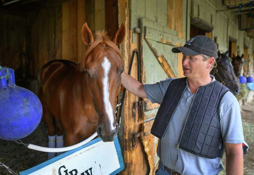 Trainer George Weaver gives his Oaks filly Point of Honor a pat on the neck at his barn at the Oklahoma Training track adjacent to the Saratoga Race Course for morning exercise Thursday July 18 2019 in Saratoga Springs, N.Y. Special to the Times Union by Skip Dickstein