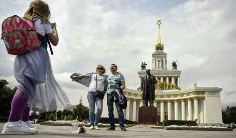 People pose for pictures by a monument to the Soviet Union founder Vladimir Lenin in front on the main building of VDNKh park in Moscow on July 16, 2019. - The Stalin-built permanent general purpose trade show and amusement park VDNKh celebrates its 80th anniversary this year. (Photo by Alexander NEMENOV / AFP)ALEXANDER NEMENOV/AFP/Getty Images