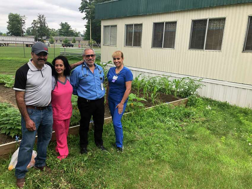 From left to right, groom Juan Torres, nurse Lucy Mercado-Freund, Dr. Alexander Cardiel, and patient care coordinator Migdalia Torres pose outside the health clinic of non-profit organization Backstretch Employee Service Team of NY (BEST) at the Saratoga Race Course on Thursday, July 18, 2019.