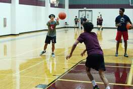 Desmond Olivier and Adolphus Evans participate in a passing drill at the Pearland summer basketball camp.