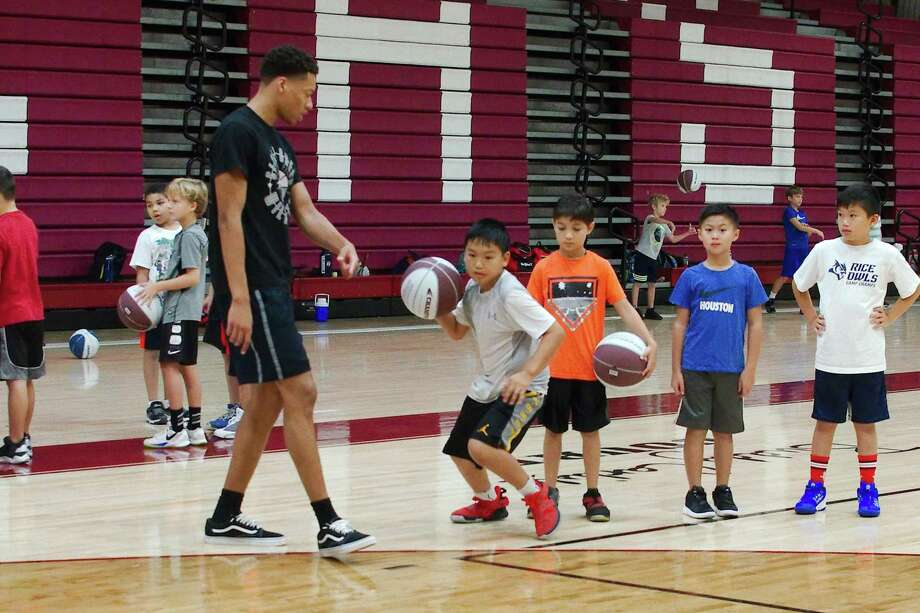 Former Clear Creek basketball player Calen Anderson assists Brandon Trinh with a drill at the Clear Creek summer basketball camp Wednesday. Photo: Kirk Sides / Staff Photographer / © 2019 Kirk Sides / Houston Chronicle