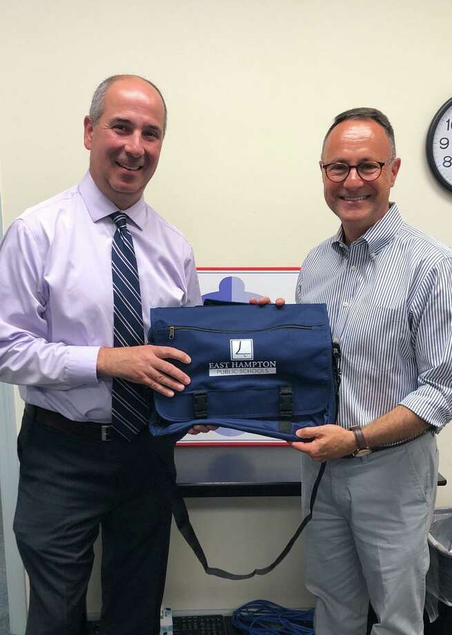 New East Hampton High School Principal Eric Verner, l, receives a book bag from Superintendent of Schools Paul K. Smith. Photo: Jeff Mill / Hearst Connecticut Media