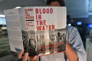 "A reporter poses in a Washington newsroom with the book ""Blood In The Water"" in Washington, DC September 1, 2016. (PAUL J. RICHARDS/AFP/Getty Images)"