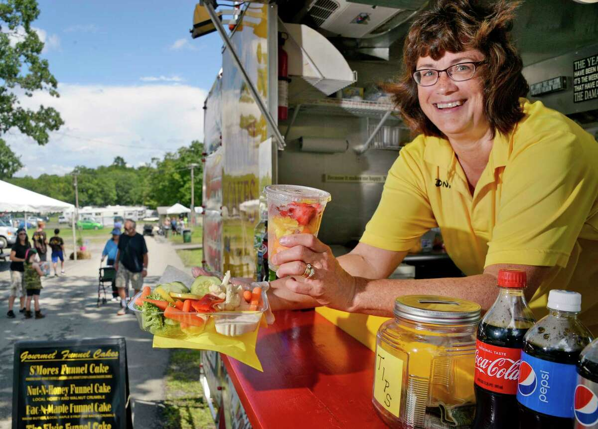 Donna Sharpe of Brett's Fried Food offers up a fresh vegetable platter and fruit cup at the Altamont Fair Tuesday August 14, 2018 in Altamont, NY. (John Carl D'Annibale/Times Union)