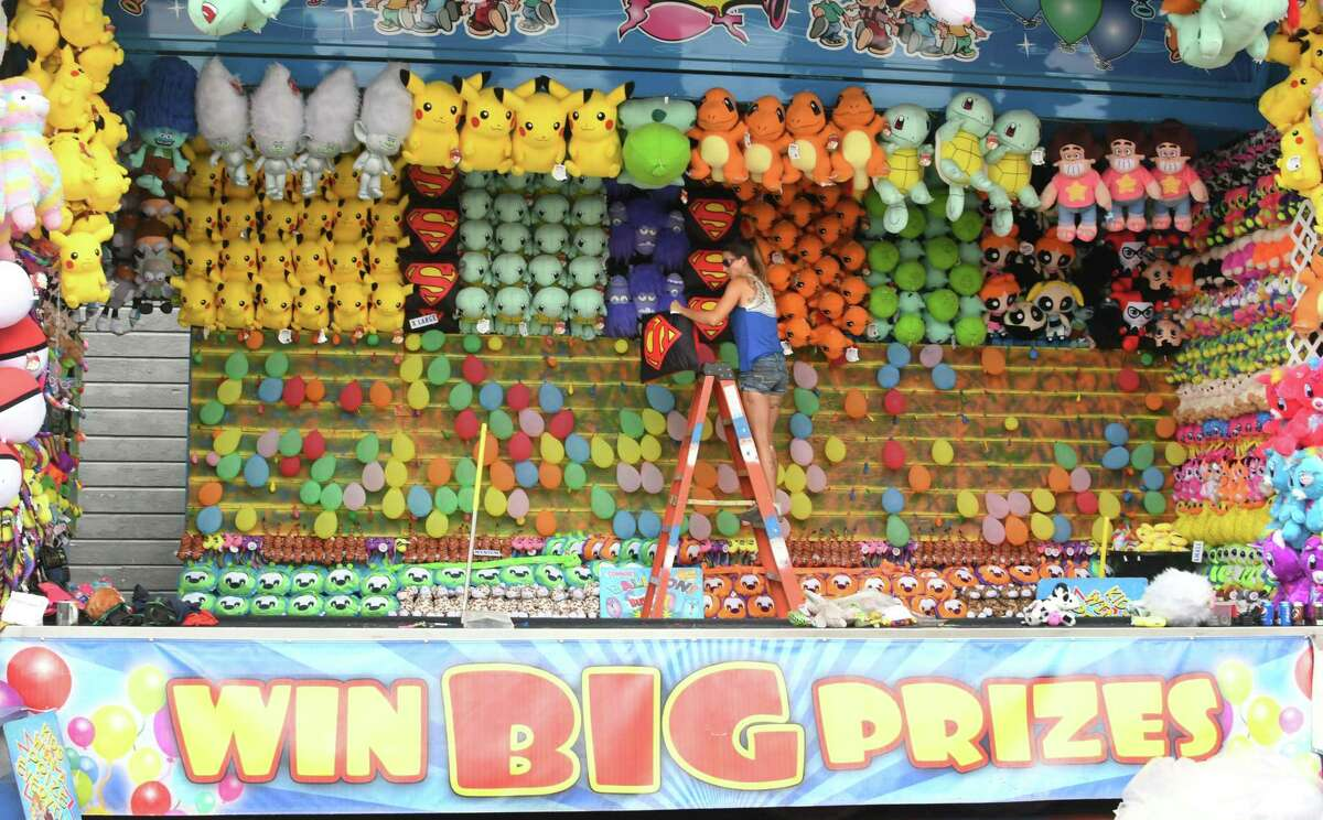 A woman hangs up prizes at the Schoharie County Sunshine Fair on Tuesday, Aug. 7, 2018 in Cobleskill, N.Y. (Lori Van Buren/Times Union)