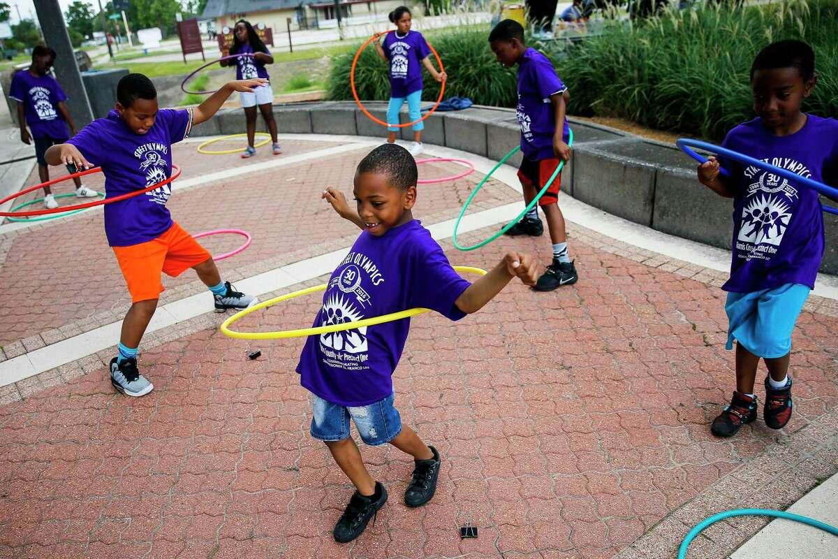 Ardyn Harrison, 7, laughs while hula hooping during the opening ceremonies of the 30th annual Harris County Precinct 1 Street Olympics at Mickey Leland Memorial Park Friday, June 10, 2016 in Houston. Commissioner El Franco Lee founded the event in 1986.