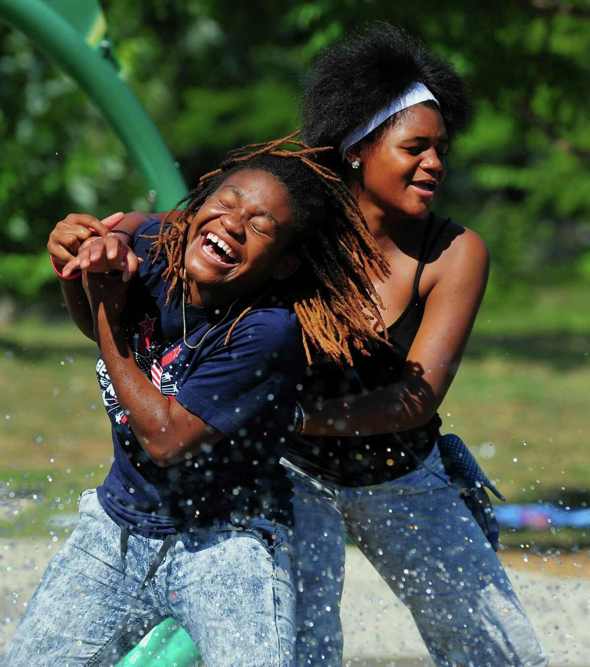 Mikea Curry, 15, gets pushed into a stream of water by her friend Destinee Williams, 14, as they play at the splash pad at the Luis Munoz Marin Park on Helen Street in Bridgeport, Conn., on Tuesday Aug. 4, 2015.