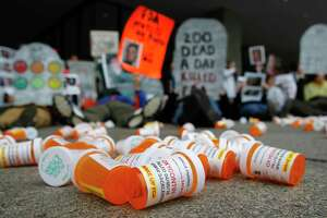 In this April 5, 2019, file photo, containers depicting OxyContin prescription pill bottles lie on the ground in front of the Department of Health and Human Services' headquarters in Washington as protesters demonstrate against the FDA's opioid prescription drug approval practices.