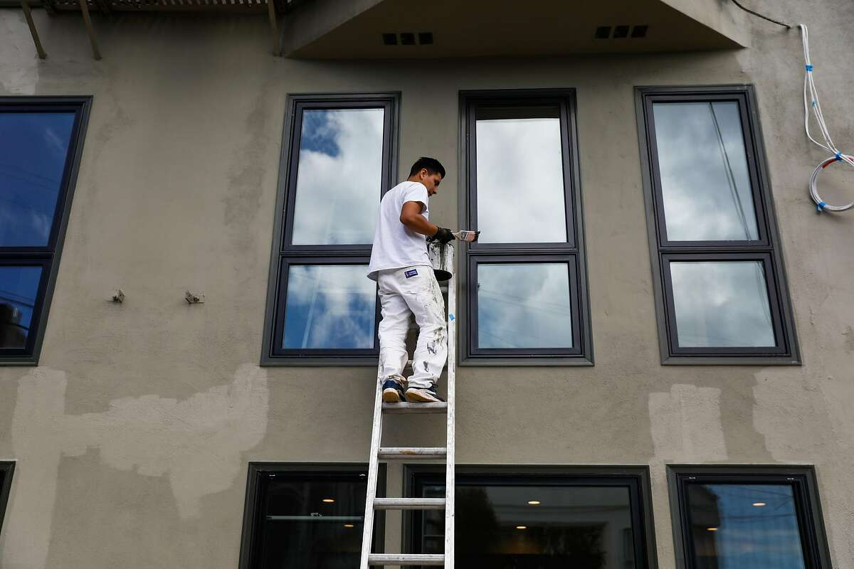 Construction worker Anelson Mejia puts the finishing touches on the exterior of an apartment that was converted from a garage into an rental unit on Roanoke Street in San Francisco, California, on Tuesday, March 26, 2019.