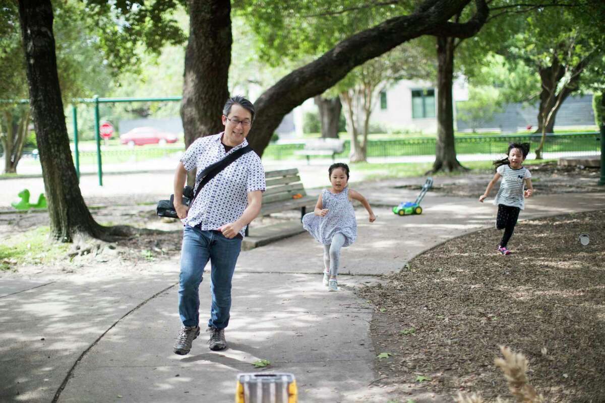 """Hideaki Takahashi plays tag with his daughter Nao Takahashi, 5, at the Old Braeswood Park on Wednesday, May 22, 2019, in Houston. """"There is an inclusive atmosphere,"""" he said of the neighborhood, where his family has lived for three years. He supported the Old Braeswood Property Owners Association's efforts to remove an unenforced restriction on the race of people who could live there."""