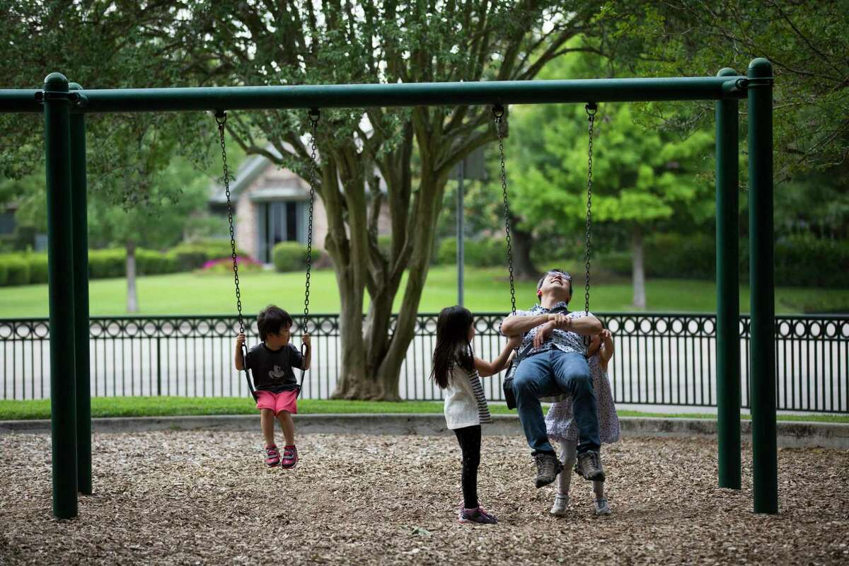 Kanin Arimura, 6, and Nao Takahashi, 5, push Hideaki Takahashi in the swing at the Old Braeswood Park on Wednesday, May 22, 2019, in Houston. They are all Old Braeswood residents.