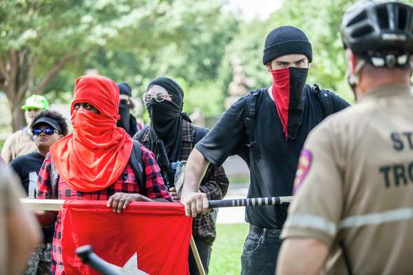 Antifa International members stare down the state troopers during a counter white supremacy march to the Capitol in Austin, Texas on September 23, 2017.