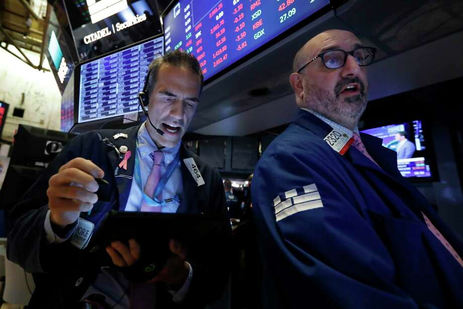 Trader Gregory Rowe, left, and specialist Peter Giacchi work on the floor of the New York Stock Exchange, Thursday, July 18, 2019. U.S. stocks moved lower in early trading on Wall Street Thursday after Netflix reported a slump in new subscribers and dragged down communications companies. (AP Photo/Richard Drew) Photo: Richard Drew / Copyright 2019 The Associated Press. All rights reserved.