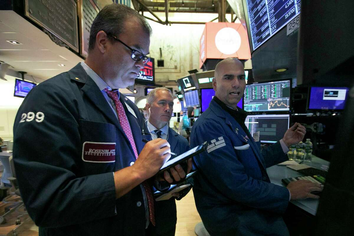 Traders William Lawrence, left, Timothy Nick, center, and specialist Philip Finale work on the floor of the New York Stock Exchange, Thursday, July 18, 2019. U.S. stocks moved lower in early trading on Wall Street Thursday after Netflix reported a slump in new subscribers and dragged down communications companies. (AP Photo/Richard Drew)