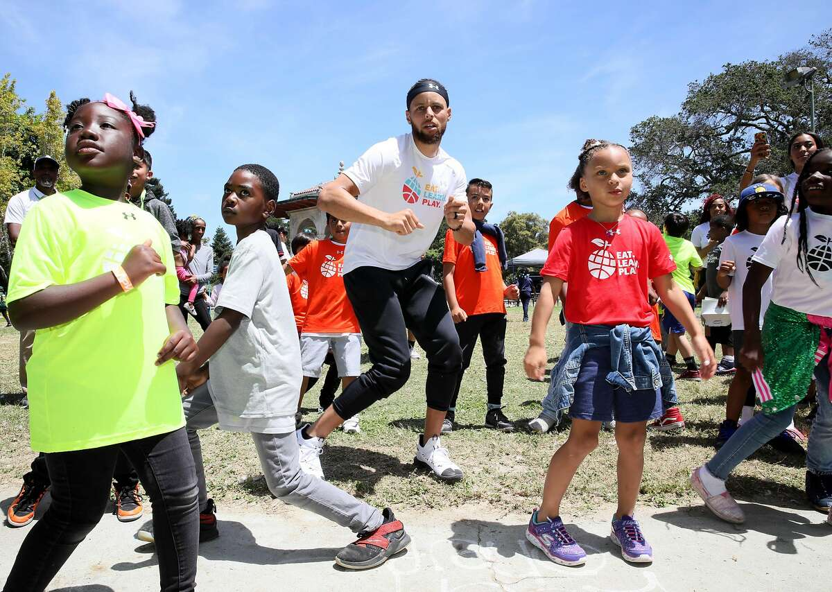 Golden State Warriors guard Stephen Curry dances with his daughter Riley (second from right in red t-shirt), who turns 7 this week, during the launch of Eat, Play, Learn, at Lakeside Park at Lake Merritt in Oakland, Calif., on Thursday, July 18, 2019. Curry and his wife Ayesha started the new foundation that focuses on providing support for the 3 basic ingredients of a healthy childhood. They are partnering with Oakland Parks and Recs and other local entities to provide services for underserved Oakland children.