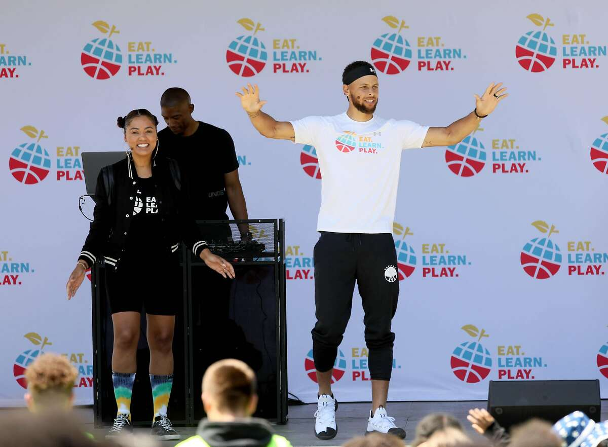 Ayesha Curry stands on stage with her husband, Golden State Warriors guard Stephen Curry, during the launch of Eat, Play, Learn, at Lakeside Park at Lake Merritt in Oakland, Calif., on Thursday, July 18, 2019. The couple started the new foundation that focuses on providing support for the 3 basic ingredients of a healthy childhood. They are partnering with Oakland Parks and Recs and other local entities to provide services for underserved Oakland children.