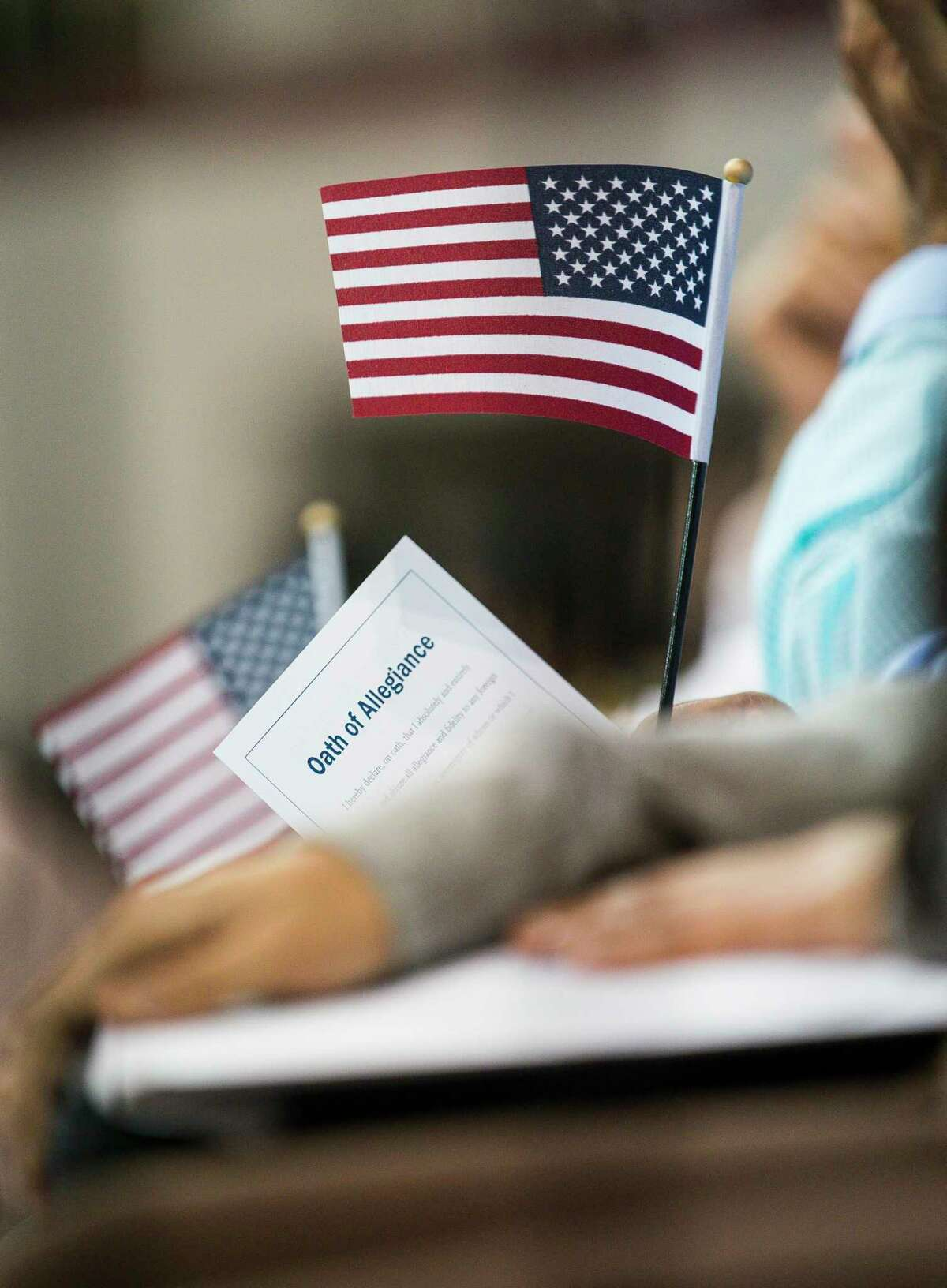 A new citizen holds their oath of allegiance and an American flag after becoming a naturalized United States citizen during a ceremony at the M.O. Campbell Education Center in Houston, Wednesday, July 10, 2019. 2,382 new citizens wore sworn in during the ceremony.