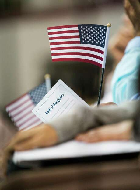 A new citizen holds their oath of allegiance and an American Flag after becoming a naturalized United States citizens during a ceremony at the M.O. Campbell Education Center in Houston, Wednesday, July 10, 2019.