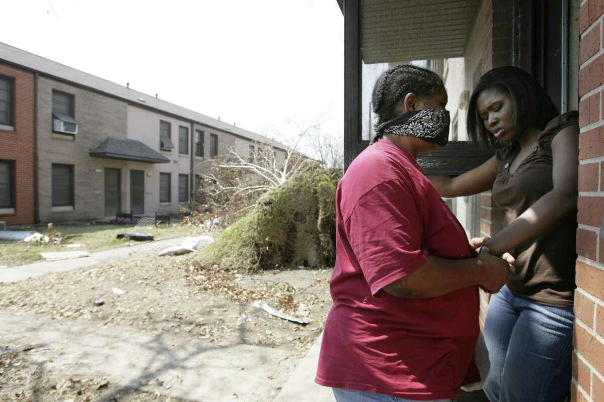 Stephany Brown helps her blind aunt, Sarah Horn, enter Horn's apartment on the destroyed bottom floor at the Oleander Homes destroyed by Hurricane Ike in September 2008.