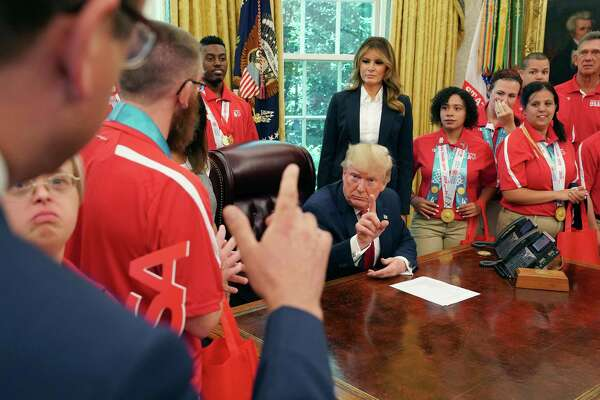 WASHINGTON, DC - JULY 18: U.S. President Donald Trump (C) answers questions from ABC News' Jonathan Karl (L) as Trump and first lady Melania Trump host members of the United States Special Olympics World Games team in the Oval Office at the White House July 18, 2019 in Washington, DC. During the photo opportunity, Trump said that he wished his supporters had not chanted, 'Send her back,' in reference to Rep. Ilhan Omar (D-MN) during a political rally Wednesday in North Carolina. (Photo by Chip Somodevilla/Getty Images) ***BESTPIX***