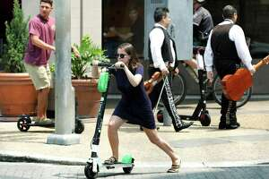 Scooter riders at Presa and West Commerce streets last May. San Antonio has banned riding the dockless vehicles on sidewalks since July 1 and police are holding off on ticketing during a grace period to educate riders.