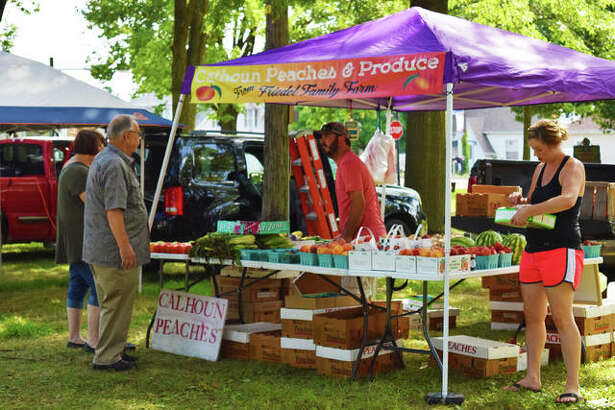 A Maryville couple looks over some Calhoun peaches, offered at the Maryville Farmers' Market on Thursday.
