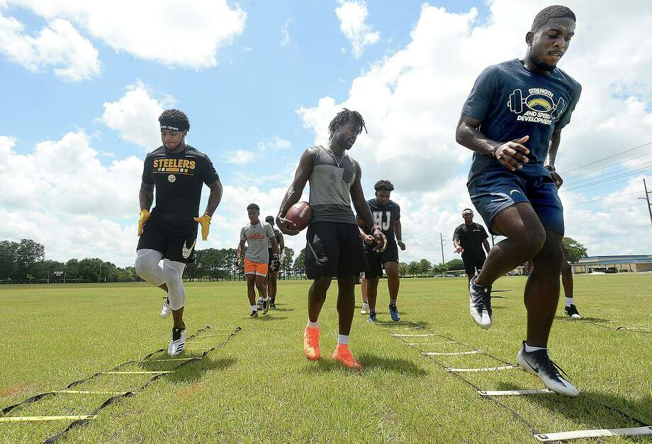 NFL players and Southeast Texas natives Rodney Randle, Jr., (right) and P. J. Locke lead drills with high school football players as Aaron Garrett (center) watches Thursday at West Brook High School. Photo taken Thursday, July 18, 2019 Kim Brent/The Enterprise Photo: Kim Brent / Kim Brent / BEN