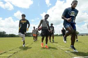 NFL players and Southeast Texas natives Rodney Randle, Jr., (right) and P. J. Locke lead drills with high school football players as Aaron Garrett (center) watches Thursday at West Brook High School. Photo taken Thursday, July 18, 2019 Kim Brent/The Enterprise