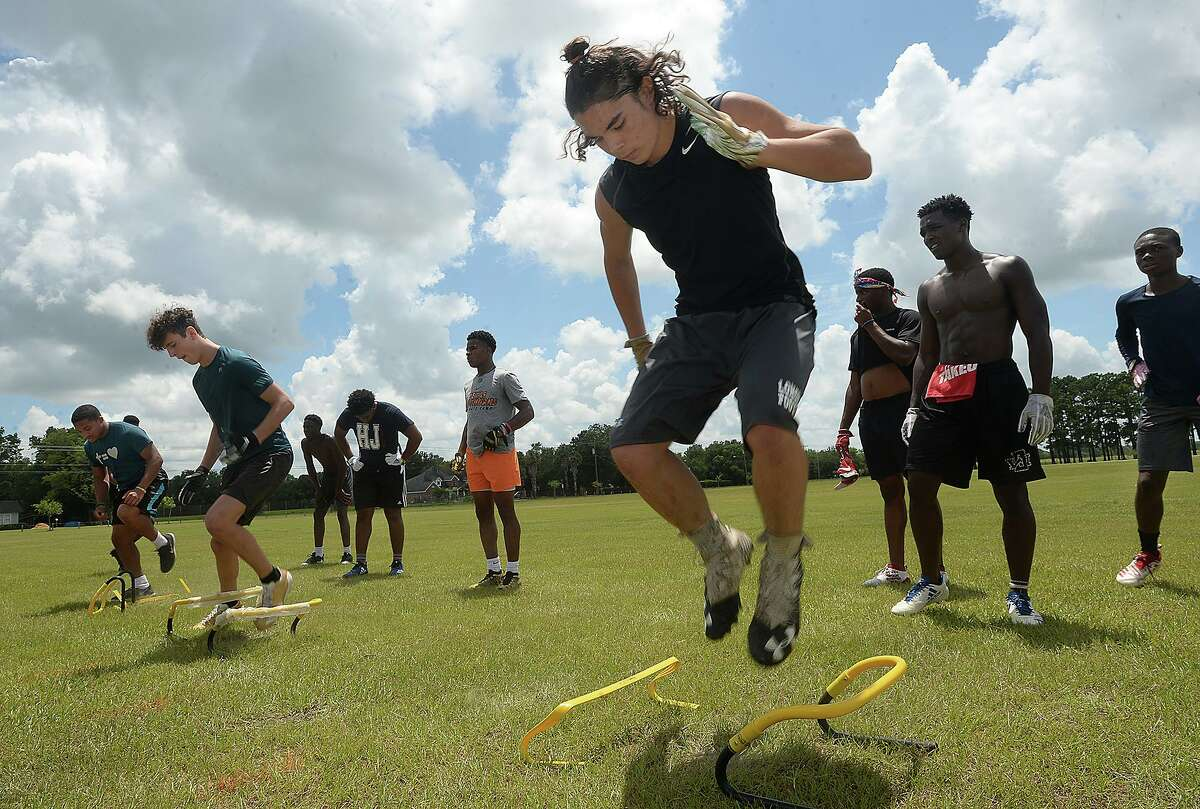 Brendan Walter (right) joins in defensive drills during a workout with NFL players and Southeast Texas natives Rodney Randle, Jr., and P. J. Locke Thursday at West Brook High School. Photo taken Thursday, July 18, 2019 Kim Brent/The Enterprise